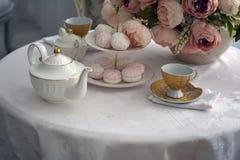 Tasses et bonbons sur la table de cuisine Photo stock