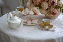 Tasses et bonbons sur la table de cuisine Photos stock