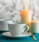 Tasses et bougies blanches sur le fond du jardin couvert de neige Image libre de droits