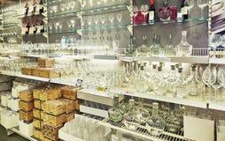 Tasses et bouteilles en verre dans le supermarché Photographie stock libre de droits