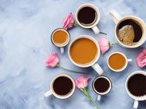 Tasses et tasses de café et de fleurs Image stock