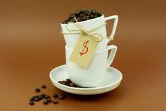 Tasses et soucoupes de café avec les grains de café et le symbole dollar d'arc Photo stock