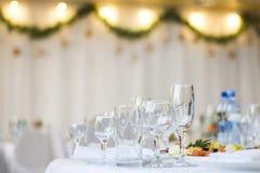 Tasses et verres en verre sur la table dans un restaurant avec un intérieur du ` s de nouvelle année Photos libres de droits