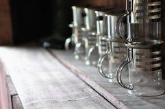 Tasses faites sur commande uniques sur l'étagère en bois Image libre de droits