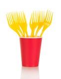 Tasses jetables lumineuses et fourchettes en plastique d'isolement sur le blanc Photo stock