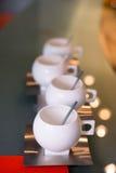 Tasses modernes de hanche avec des soucoupes et des cuillères en acier inoxydable Photo stock