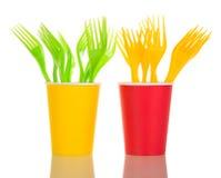 Tasses multicolores et fourchettes jetables d'isolement sur le blanc Image stock