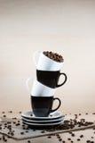 Tasses noires et blanches sur la pile des plats avec complètement des grains de café rôtis se tenant sur le journal Photographie stock