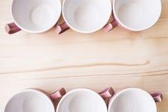 6 tasses se tenant avec des poignées dans différentes directions Images stock