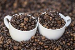 Tasses sur des haricots de coffe Image stock