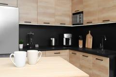 Tasses sur la table dans l'intérieur moderne confortable de cuisine photo libre de droits