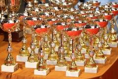 Tasses victorieuses de trophée pour des gagnants de sports sur la table Images stock