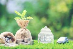 Tassi di interesse, pianta crescente sulla borsa dei soldi con la casa di modello e immagine stock