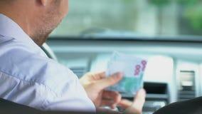Tassista amichevole che prende soldi dal cliente, servizio di taxi, trasporto stock footage