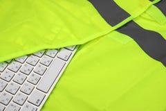 Tastatur in der gelben reflektierenden Sicherheits-Weste Stockfotografie