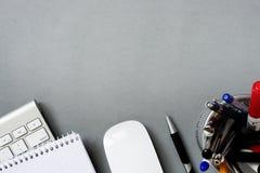 Tastatur, Maus und Stifte im Halter auf Grey Desk Lizenzfreies Stockfoto