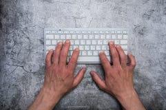 Tastatur mit den Händen auf einem dunkelgrauen Hintergrund Konkrete Tapete des Asphalts Zusammenhang, Verfasser, Programmierer, B stockbild