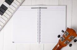 Tastatur und Gitarre mit leerem Notizbuch Stockbild