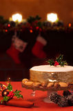 A Taste Of Christmas. Christmas cake on festive table with fireplace in background Royalty Free Stock Photos
