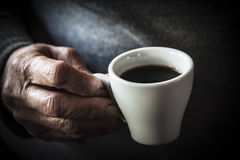 The taste of coffee. A cup of coffee is holded by the hand of an old woman Royalty Free Stock Photos