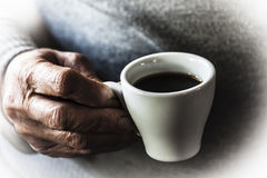 The taste of coffee. A cup of coffee is holded by the hand of an old woman Royalty Free Stock Photo