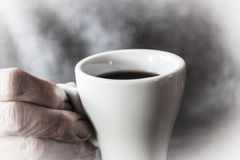 The taste of coffee. A cup of coffee is holded by the hand of an old woman Stock Image