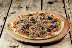 Delicious pizza. Taste the delicious pizza made of bacon mozzarella, mushrooms, and vegetables Stock Photography