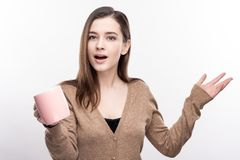 Pleasant woman suggesting trying some coffee. Taste it. Gorgeous young woman handing a cup to the camera and gesticulating emotionally, offering to try some Royalty Free Stock Photography