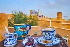 In outdoor cafe of Yazd, Iran. Taste the hot tea or coffee from traditional handmade pottery in outdoor cafe, occupying the roof in historic adobe house, Yazd royalty free stock photos