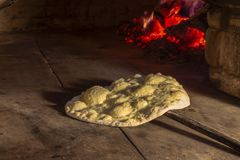 Italian bread with olive oil on the shovel in a stone furnace against the background of fire. royalty free stock photo