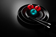The taste of New Year. A black plate in a japanese sushi restaurant menu decorated with Christmas balls and chopsticks royalty free stock photo