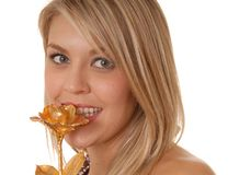 A Taste Of Rose. Lovely girl nibbling on a golden rose Royalty Free Stock Image