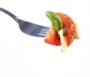 A taste of salad on a fork. Farfalle pasta, tomato, salami, mozzarella and basil Stock Images