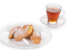 Tasteful Eclair with tea Stock Images
