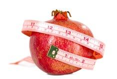 Tasteful fruit garnet with measuring tape Stock Image