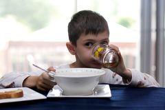 Tastefull juice. 6 year old boy having breakfast in the morning royalty free stock photos