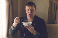Tasteless food. Bad soup. A frustrated client of restaraunt. Tasteless food. Bad soup. A frustrated and irritated man eats soup from a plate and is disappointed stock photo