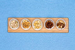 Taster dishes of assorted nuts. Containing cashews, pistachio, macadamia, hazel and brazil nuts arranged in a row on a wooden board centered on a blue Royalty Free Stock Photo