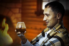 Taster. Man with glass of brandy or cognac. Taster. Young adult Man in tartan plaid holding in hand a glass of classy extra old brandy or cognac. He is inside Royalty Free Stock Photography
