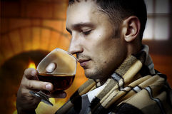 Taster. Man with glass of brandy or cognac. Taster. Young adult Man in tartan plaid holding in hand a glass of classy extra old brandy or cognac and smell it. He Royalty Free Stock Images