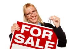 Tasti biondi attraenti della holding & per il segno di vendita Immagini Stock