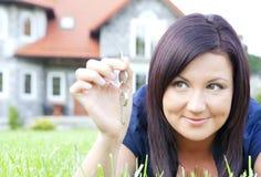 Tasti della holding della donna con la priorità bassa della casa Fotografia Stock