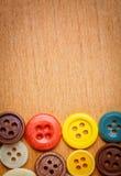 Tasti di cucito variopinti su una priorità bassa di legno Fotografia Stock Libera da Diritti