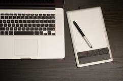 Tastiera del computer portatile e tavola dei grafici sulla tavola nera, vista superiore Fotografie Stock