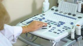 Tastiera dell'attrezzatura medica da ultrasuono Workimg irriconoscibile di medico con la macchina ultrasonica video d archivio