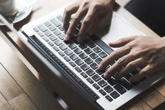Tastiera di battitura a macchina della mano sulla tavola di legno alla caffetteria immagini stock libere da diritti