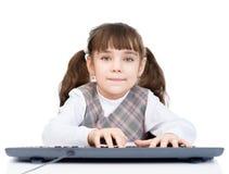 Tastiera di battitura a macchina della piccola ragazza dello studente Isolato su priorità bassa bianca Fotografie Stock Libere da Diritti