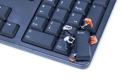 Tastiera di computer miniatura di riparazione della gente immagini stock