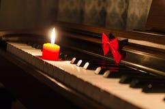 Tastiera di piano con il nastro e la candela bruciante Fotografia Stock