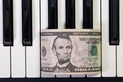 Tastiera di piano e banconota del dollaro americano Fotografie Stock Libere da Diritti